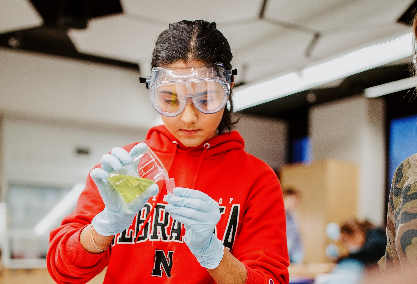 Sophia Deras transfers her solution in a Chem 109 lab to determine absorption spectra and best wavelengths in different food dyes.