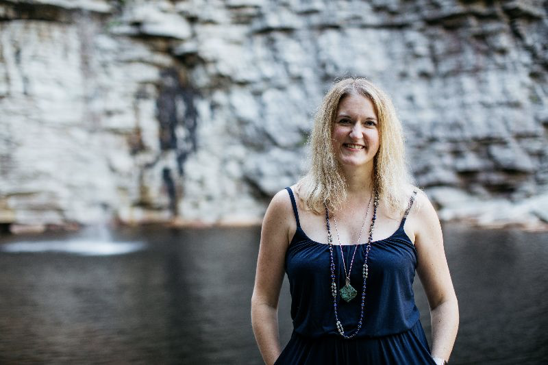 Blonde woman standing in front of a waterfall and lake, rock wall backdrop. Navy blue outfit. Happy, hands in pockets.