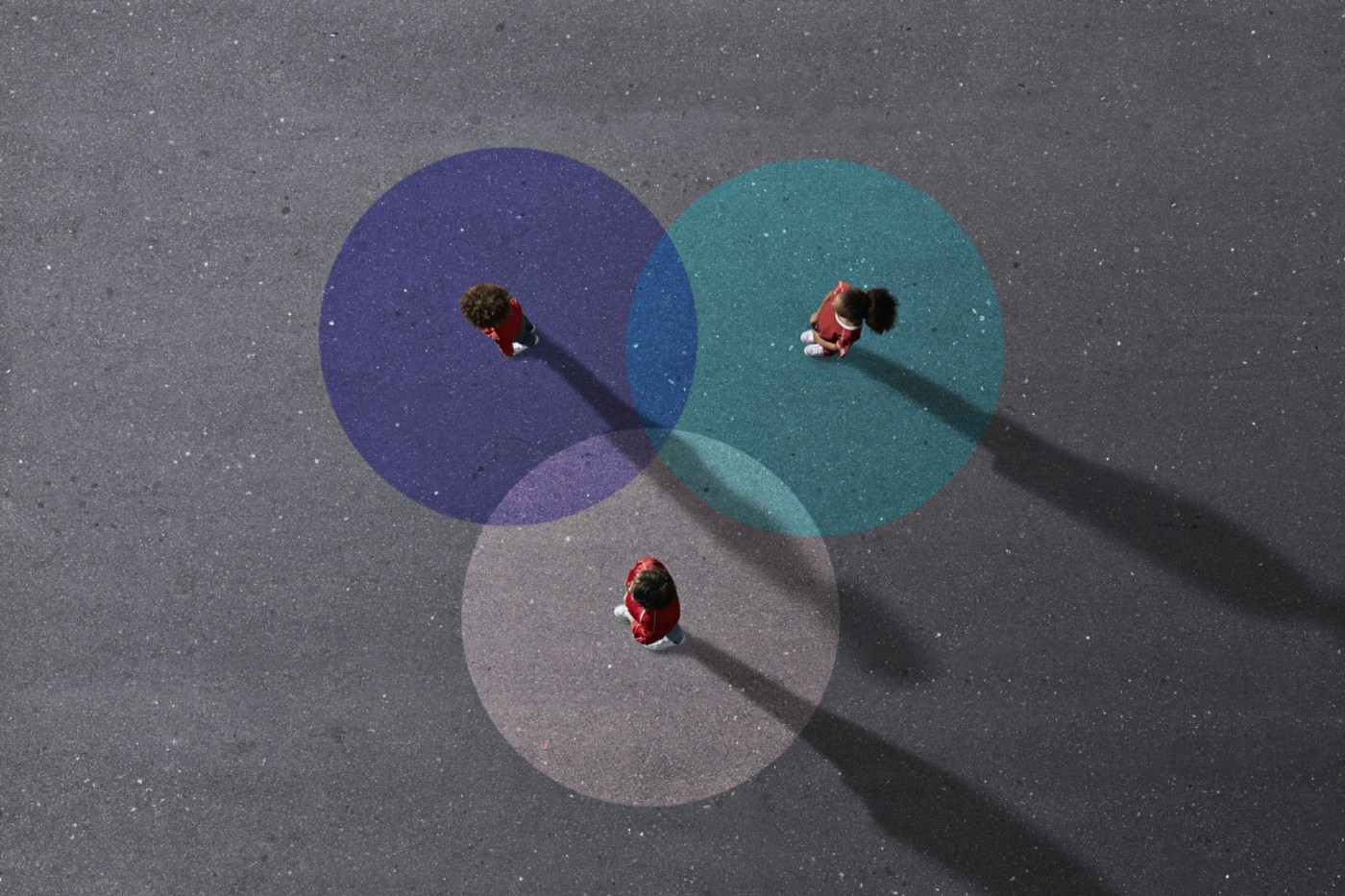 An aerial view of 3 people standing on painted Venn Diagrams.