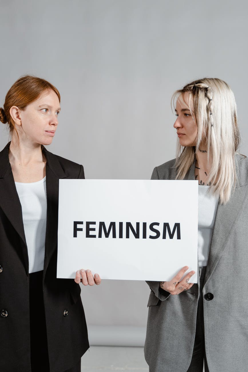 Two white women holding a feminism sign.