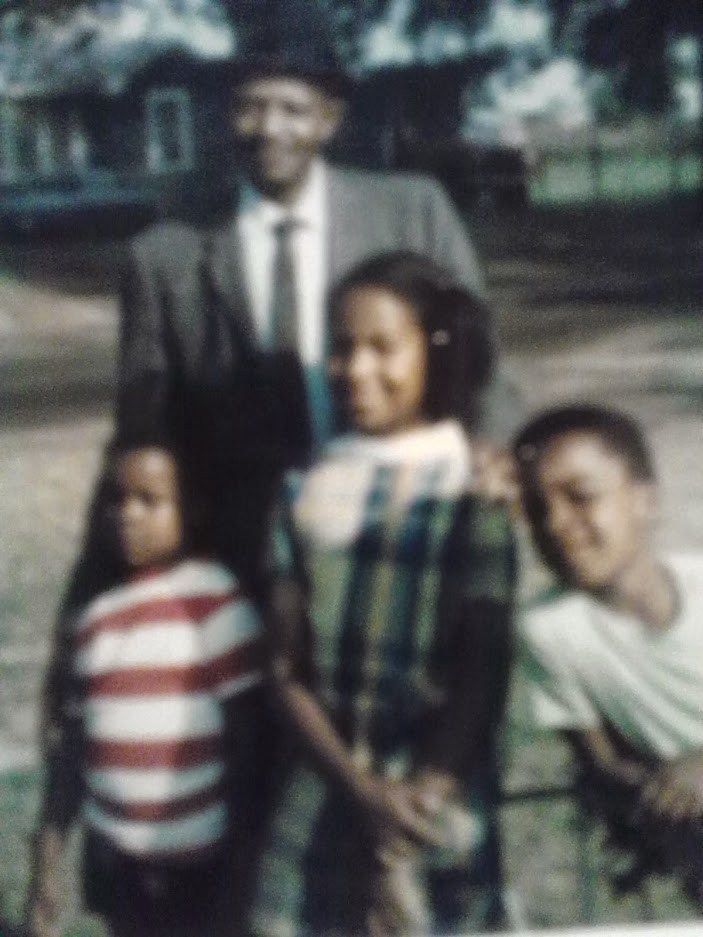 Three Black children are pictured with an adult.