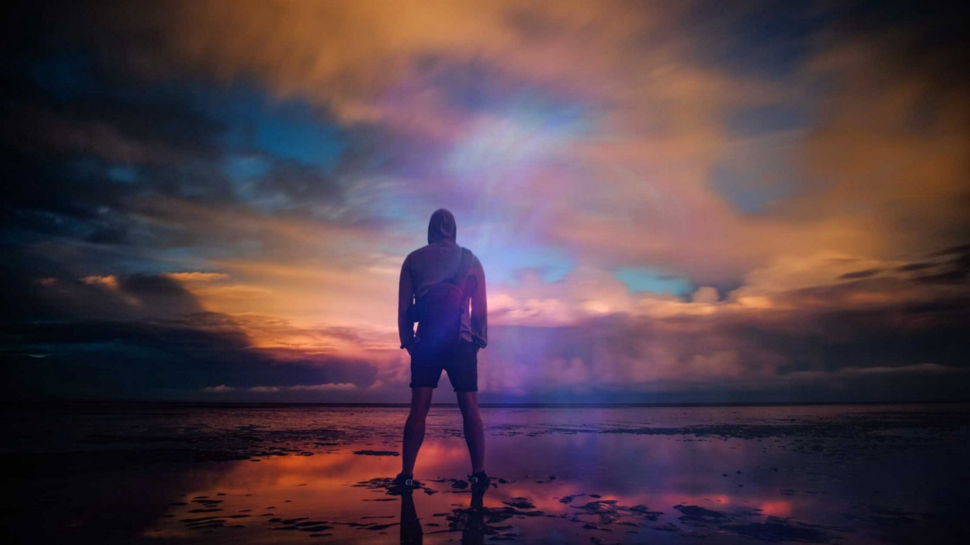 A man standing triumphant on a beach in New Romney while looking out into the water
