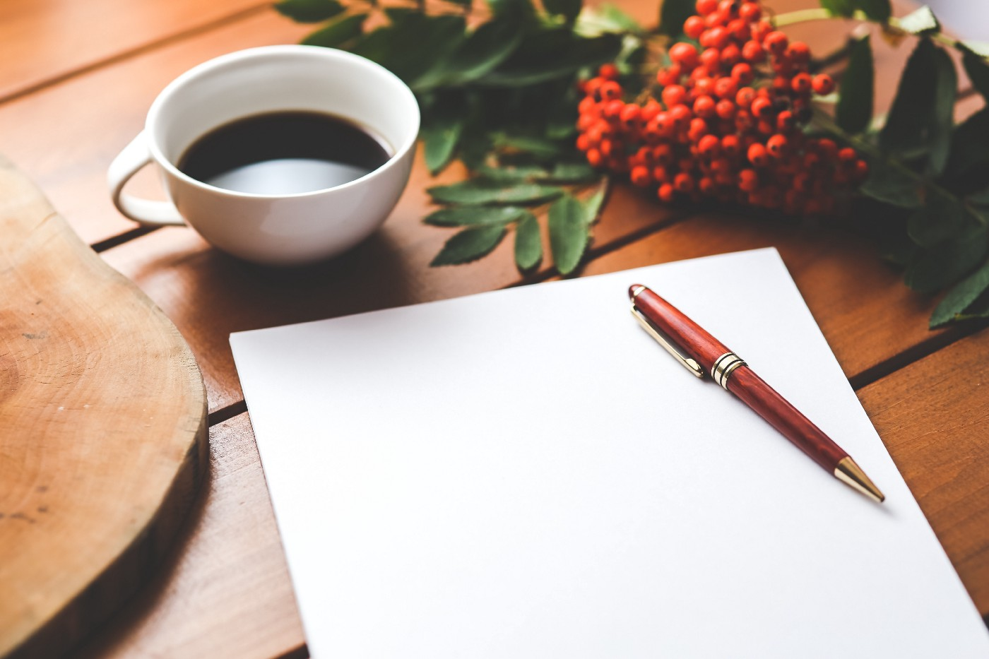 Piece of paper, a pen, and a cup of coffee.