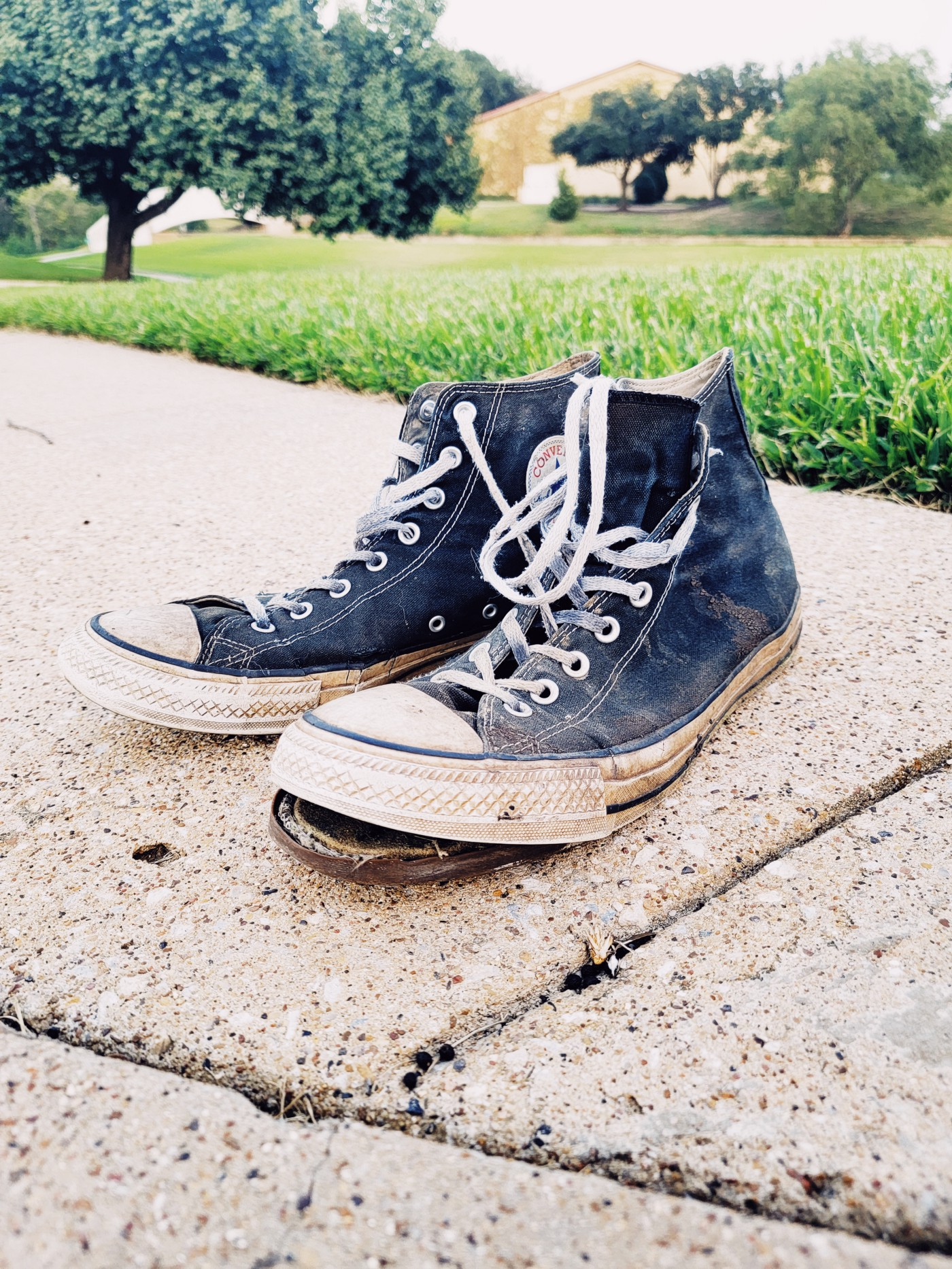 A pair of high-top sneakers in terrible shape.