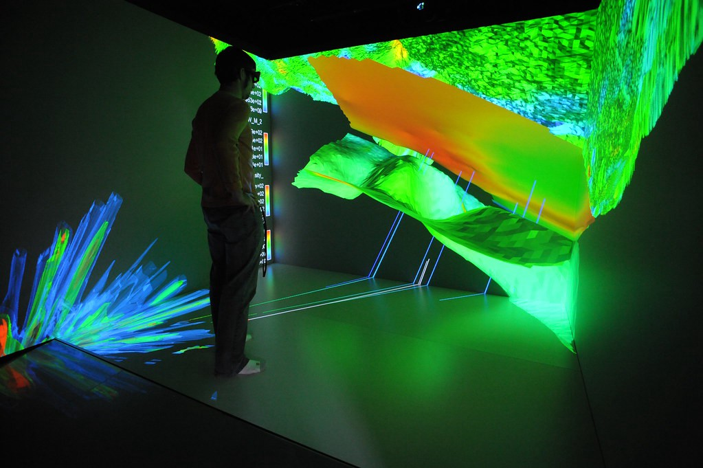 A man looking at three dimensional displayed data while he wears a headset.