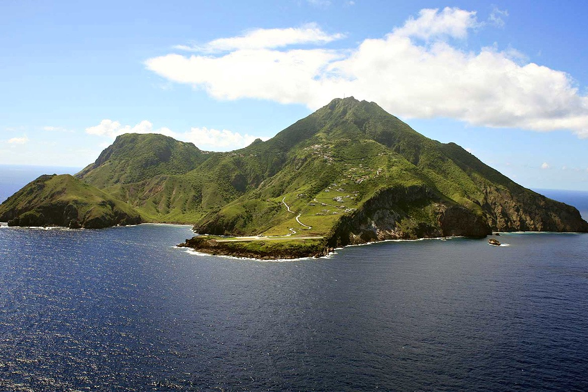 An air photo shot of the Caribbean island of Saba with deep blue sea and skies.