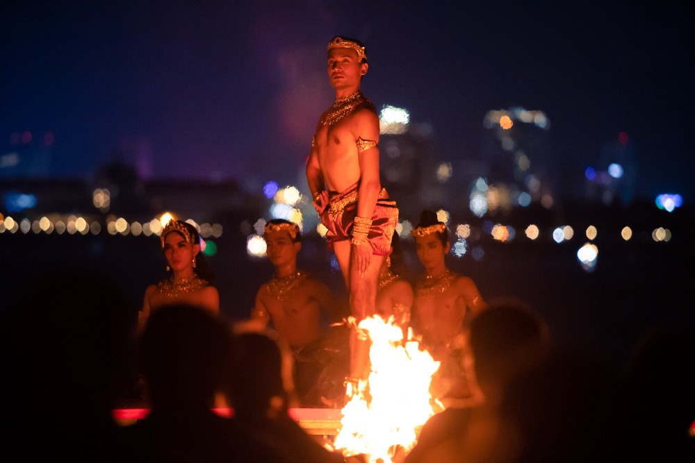 Performer in Cambodian costume, standing outside at night behind small fire