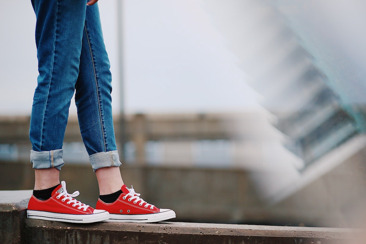 a photo of a woman's legs in rolled-up jeans and red converse low-top sneakers, balancing on a cement wall
