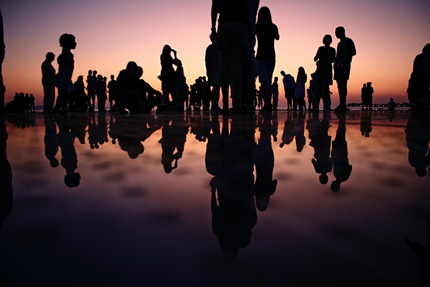 Group of people gathered at a beach at dusk, their silhouettes reflecting in the water.
