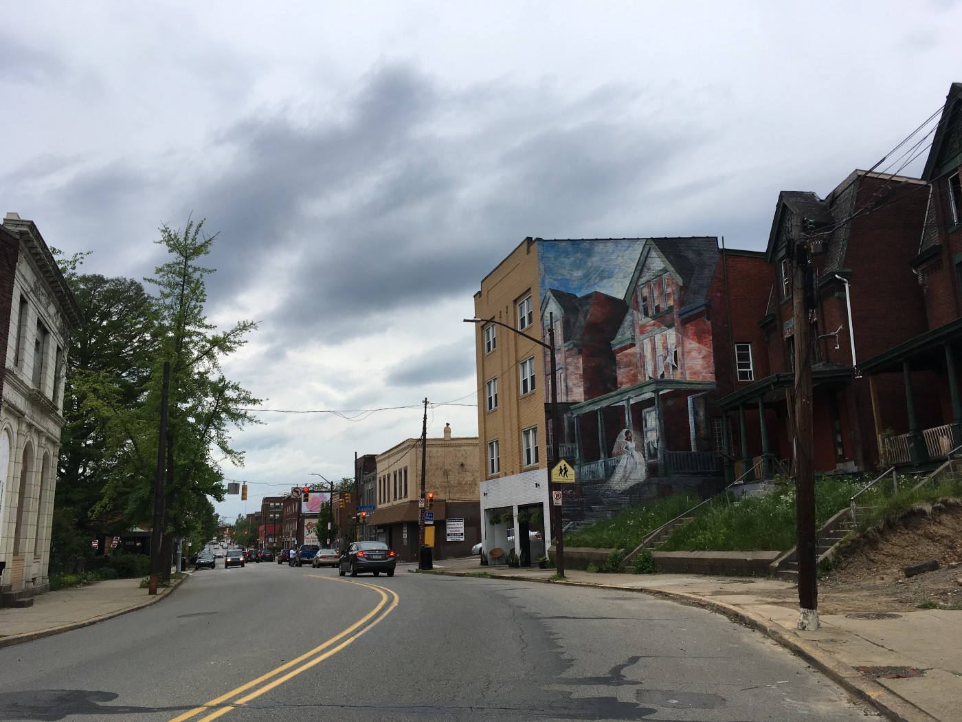 Photo of Penn Ave in Pittsburgh on an overcast day with mural of black bride in white dress on old brick building