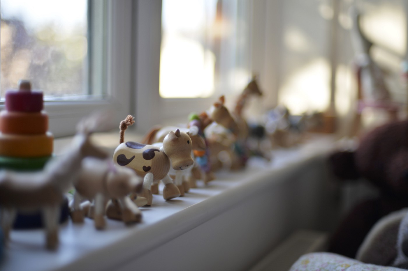 A photo of wooden animal toys lined up on a windowsill.