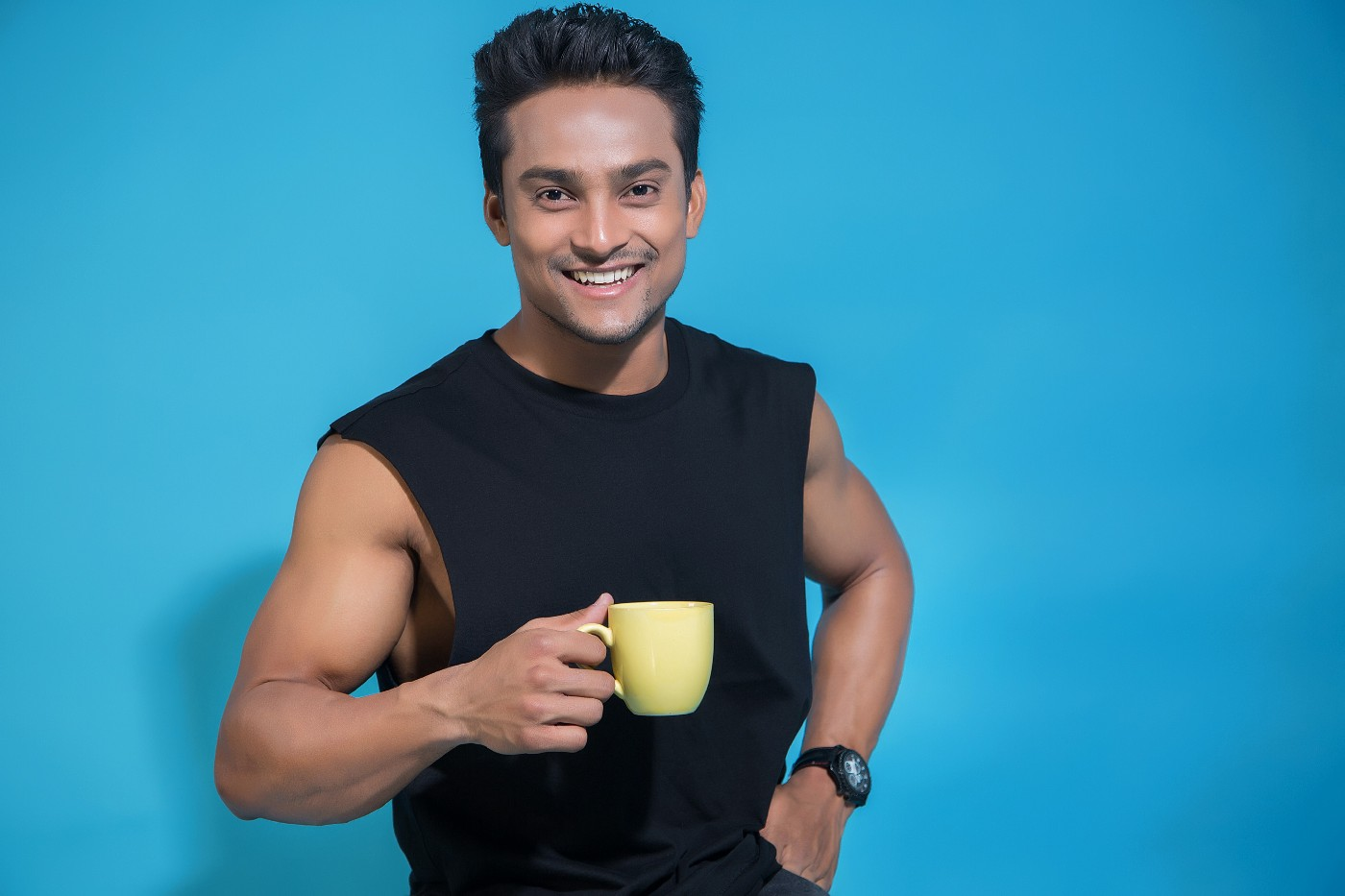 Smilingly douchey-looking person with hand on hip holding a yellow coffee mug