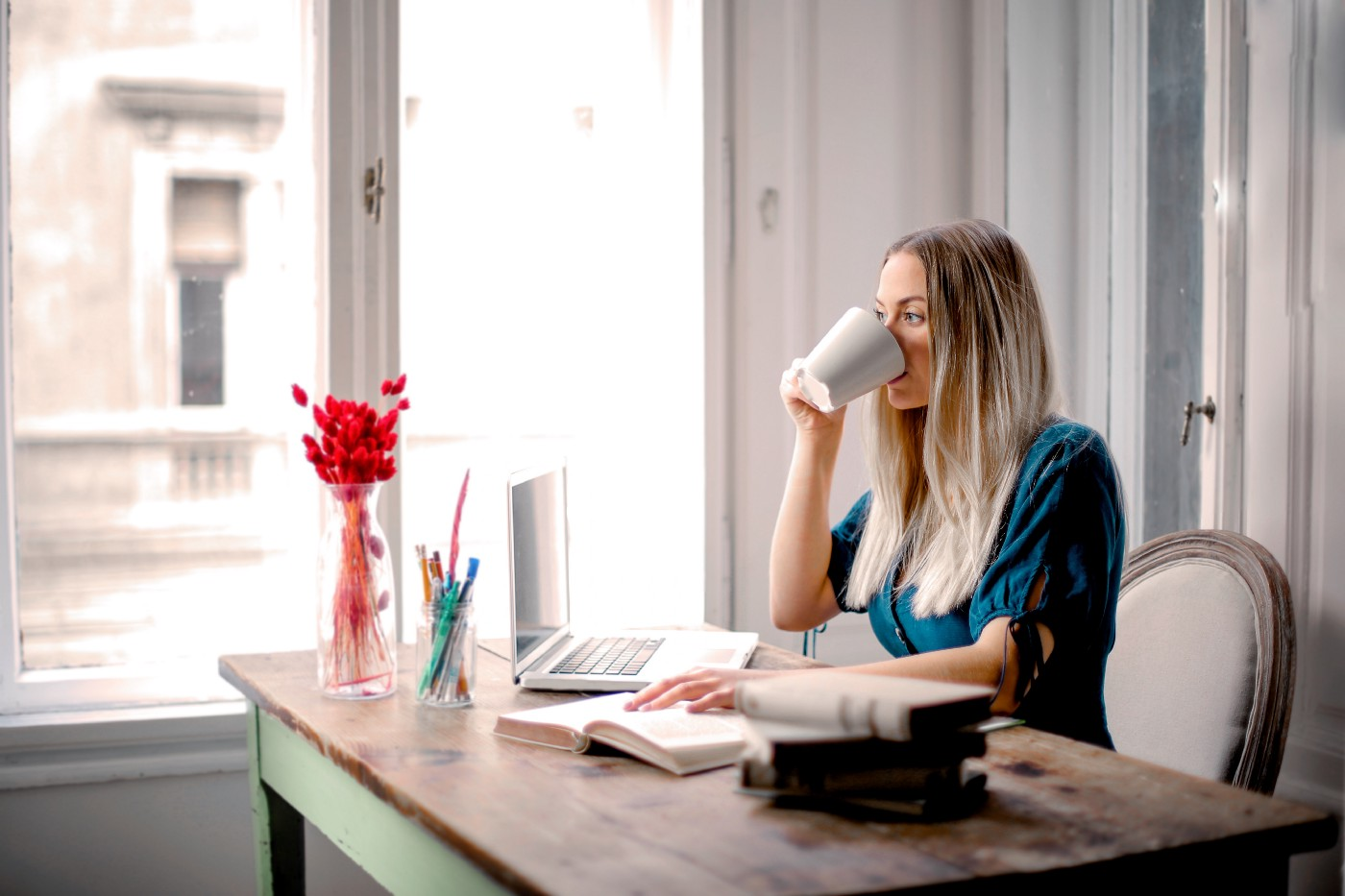 an influencer woman drinks a coffee in front of her laptop