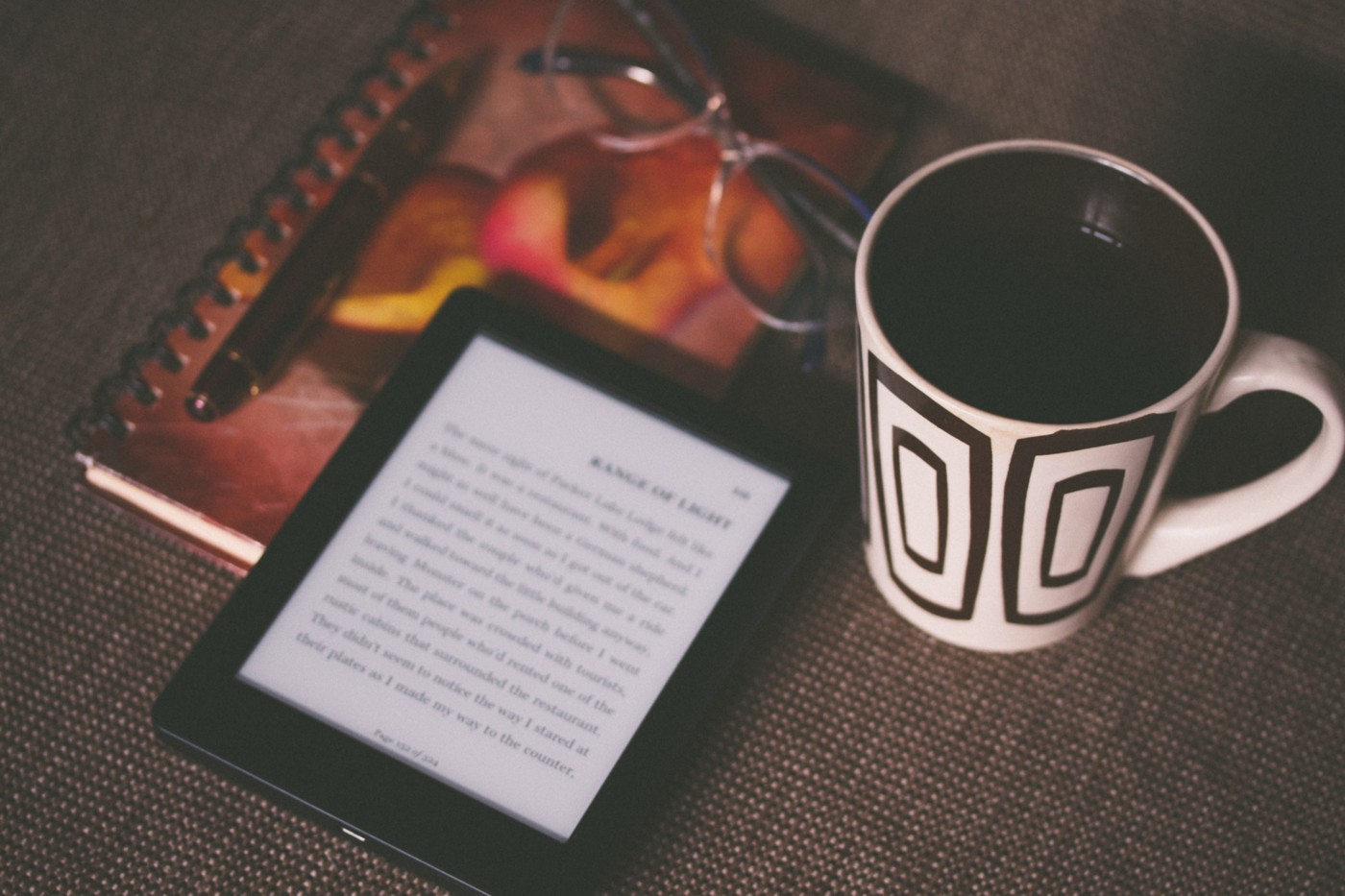 A notebook, Kindle, and mug of coffee sit on a table