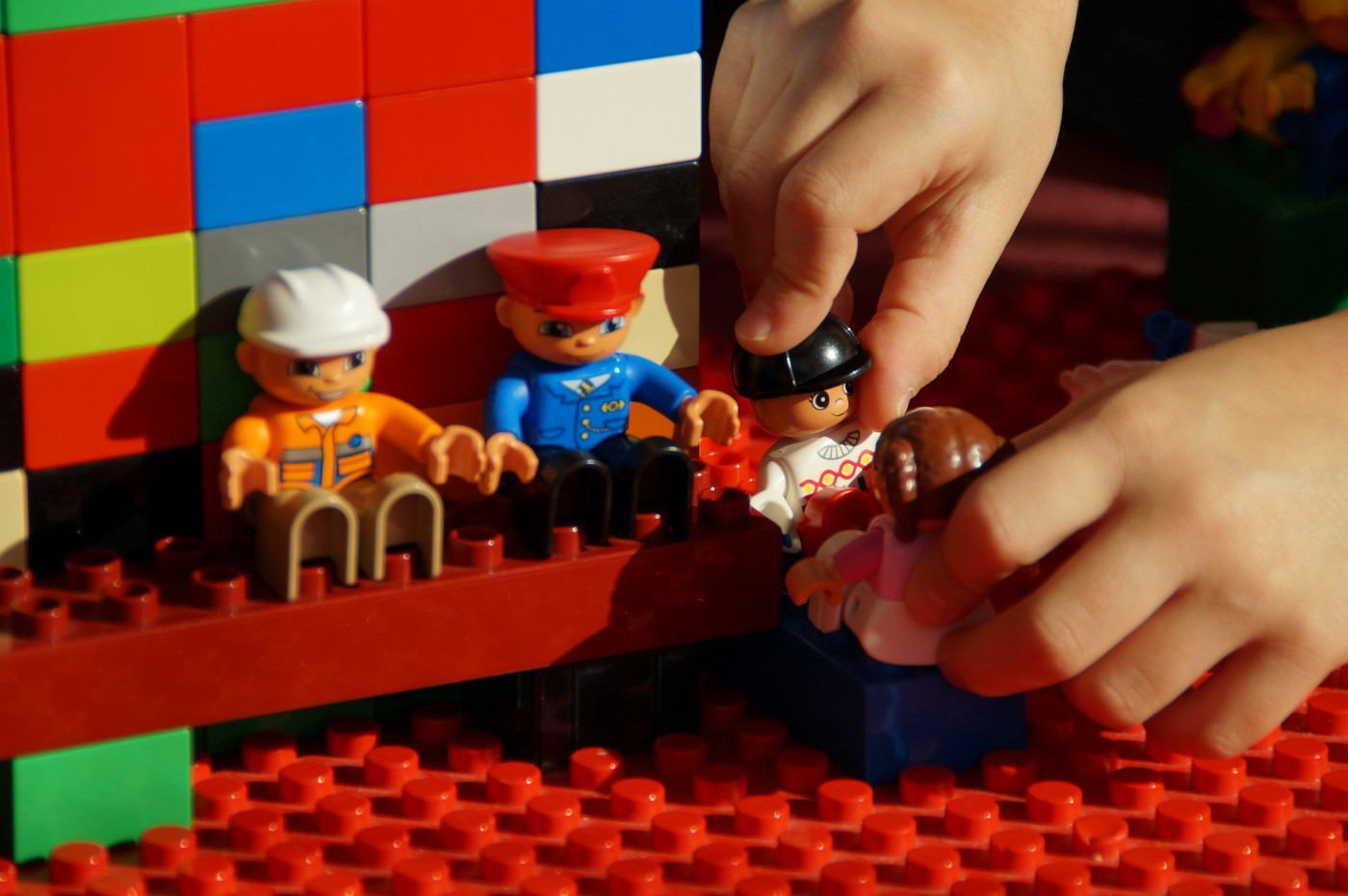 A child plays with Lego bricks and people