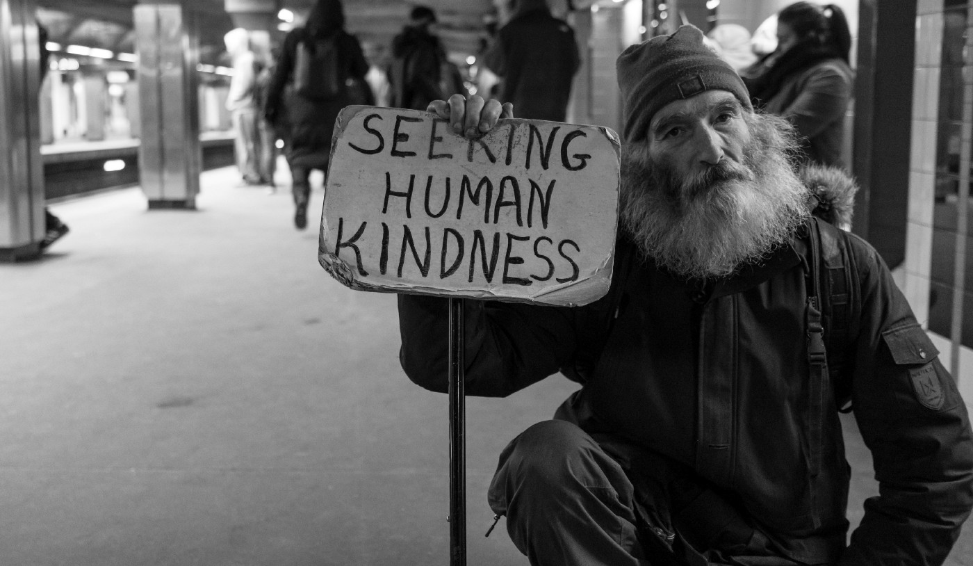 """A bearded man holding a sign that reads """"Seeking human Kindness""""."""