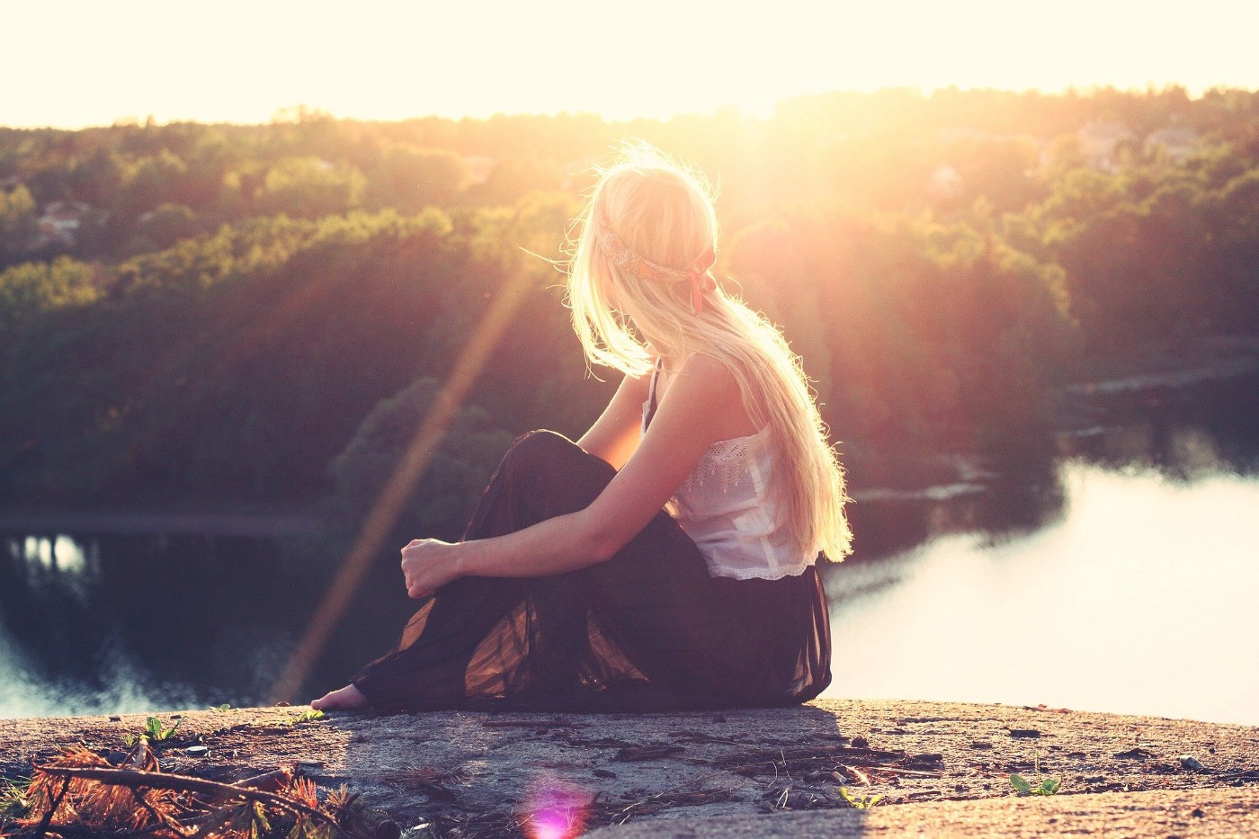 Woman looking opposite direction at the lake during sunrise