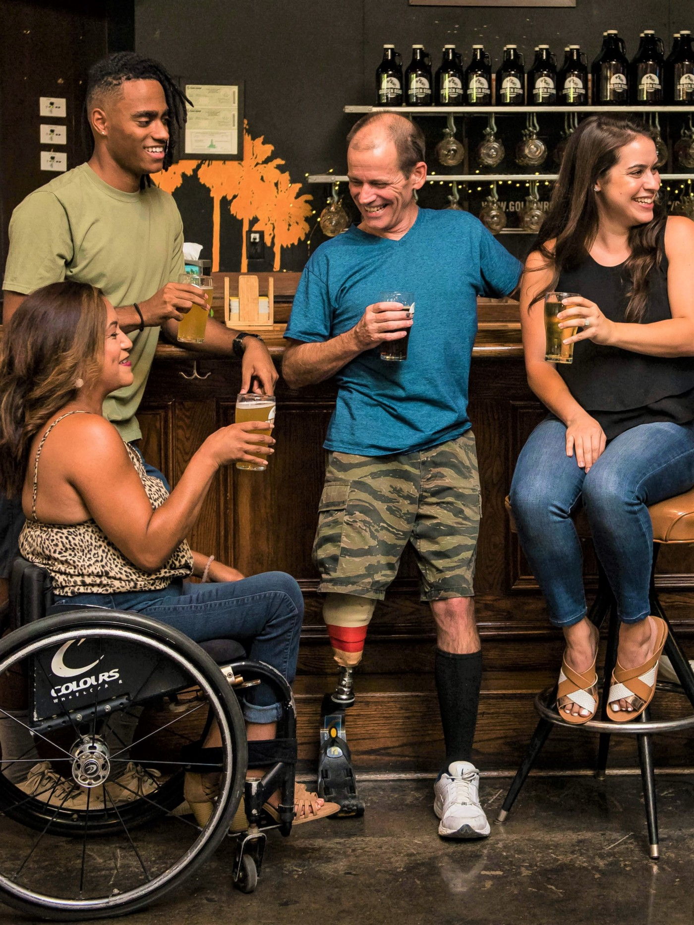 four friends in a bar drinking beer, girl in wheelchair, man with leg prosthesis