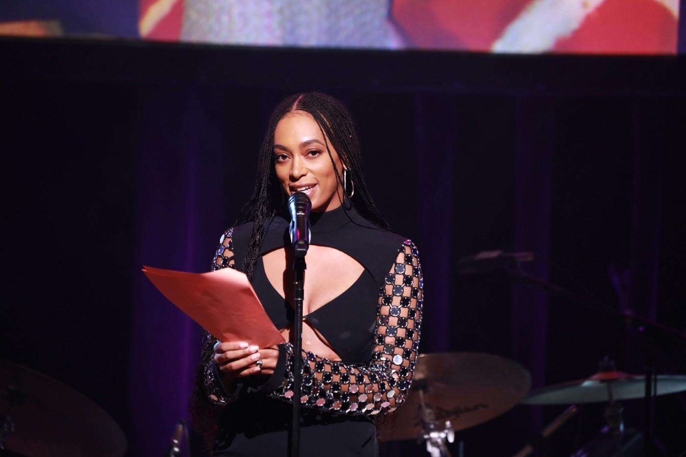 Solange accepting an award at an event.