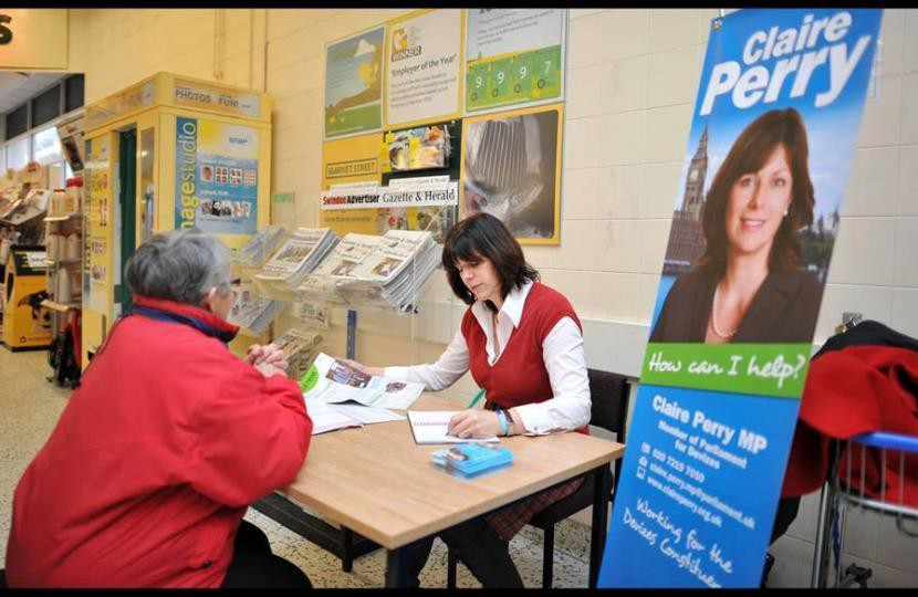 """Former MP Claire Perry conducting a constituency surgery meeting with a constituent in a public building with a poster to the left which says """"Claire Perry (headshot) How can I help?"""""""