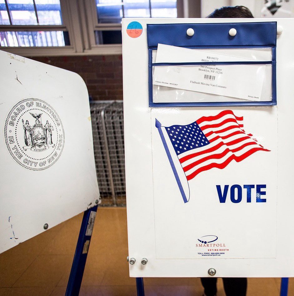 """A voting stayion a polling locayion, with an American flag and """"VOTE"""""""