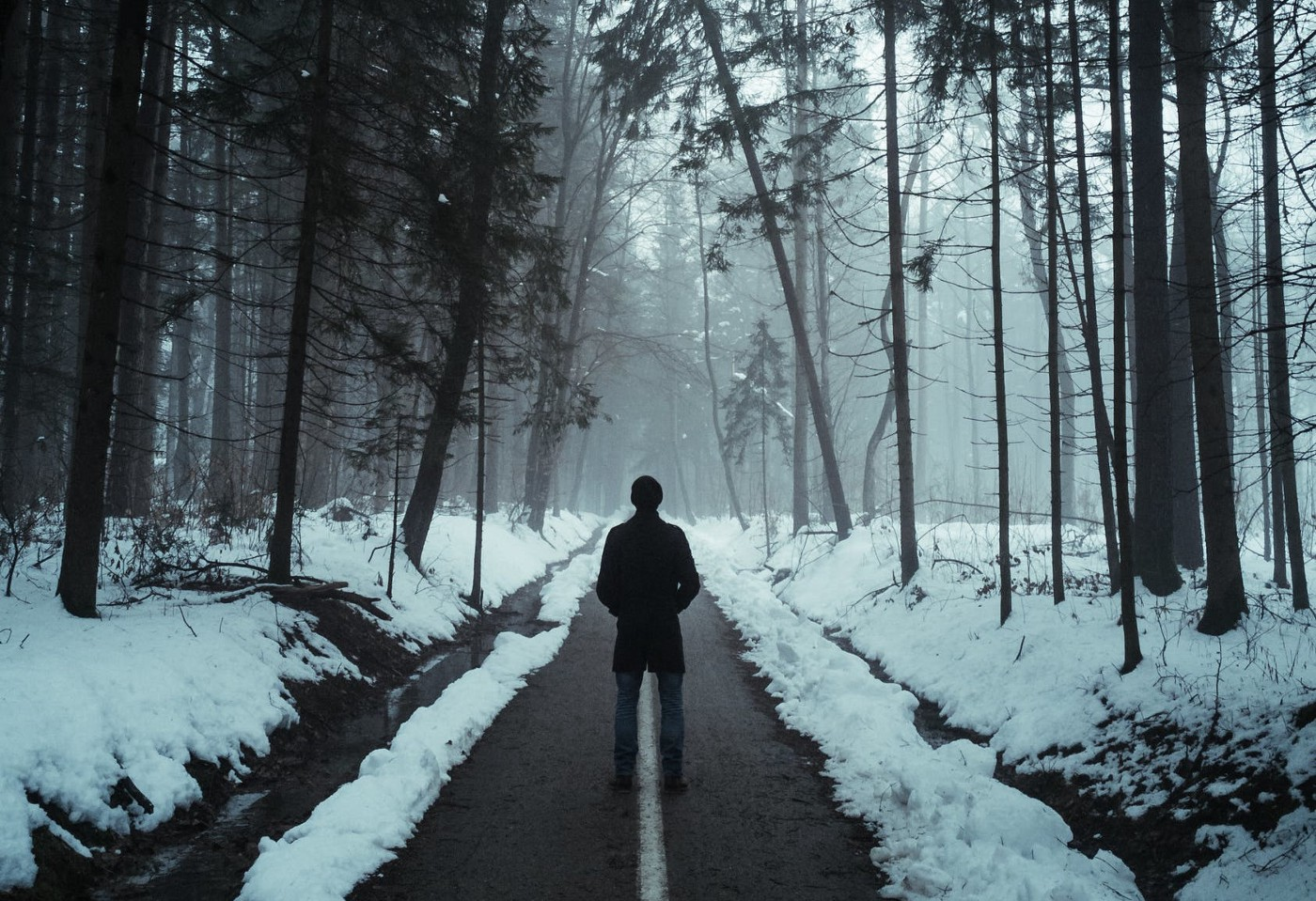 Man walking down snowy, dimly lit path