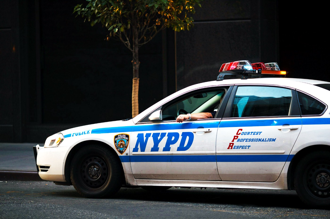 White NYPD police sedan sits at the curb