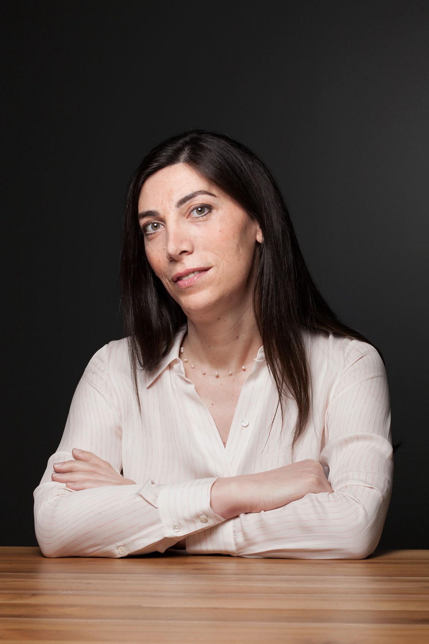 A portrait photo of Emily Leproust seated with her arms crossed at a wooden table. Leproust is CEO of Twist Bioscience.