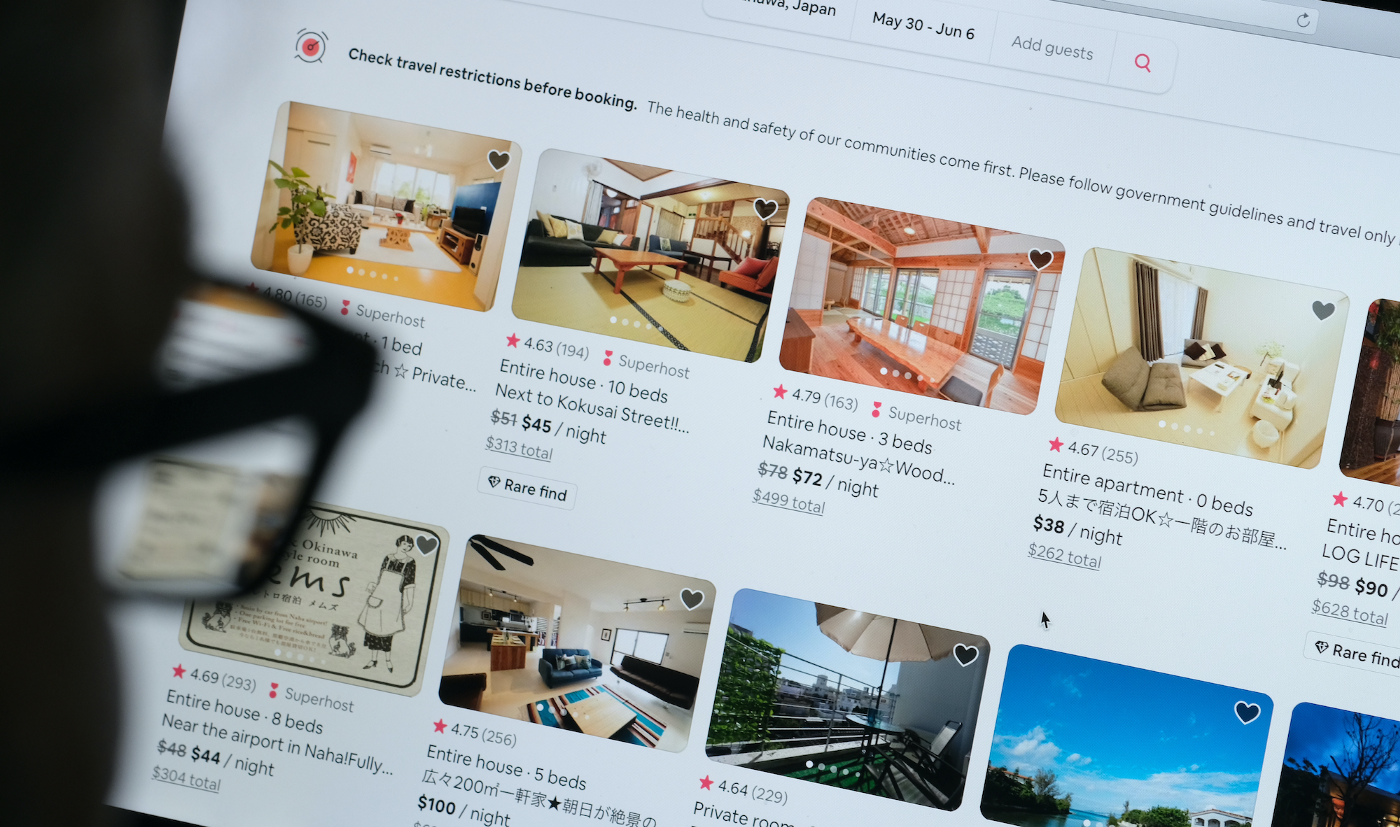 In this photo illustration, a man looks at listings on the Airbnb website.