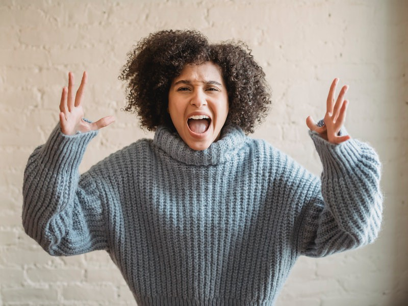 A woman in a grey sweater screaming