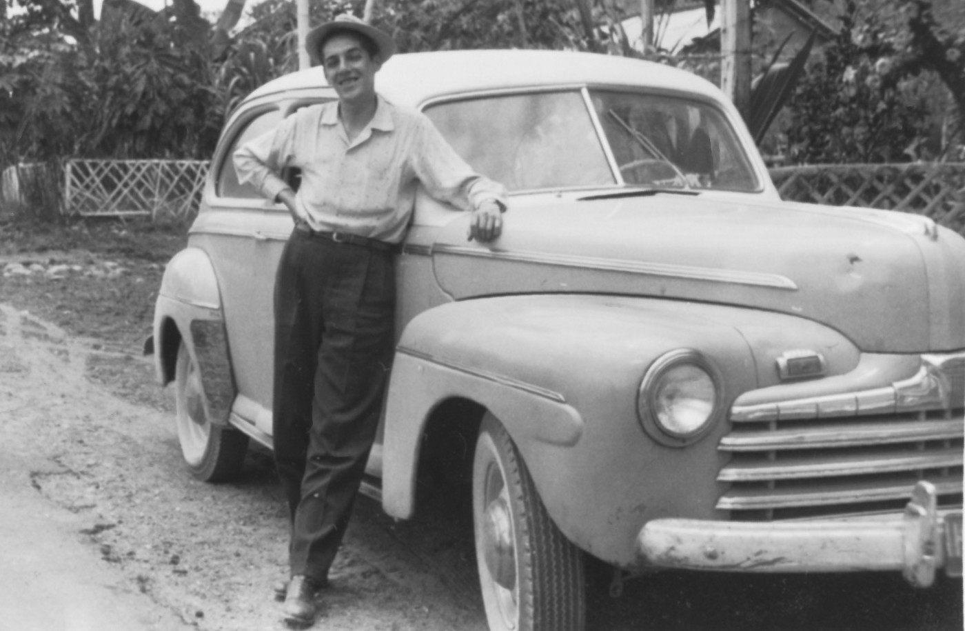 Photo of Alvaro B. Matiz posing with a 1946 Ford on the side of the road.