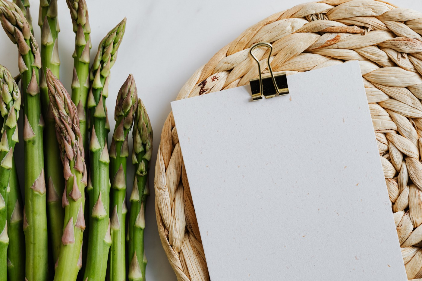 Asparagus on a table lying next to a blank paper and a brown woven mat