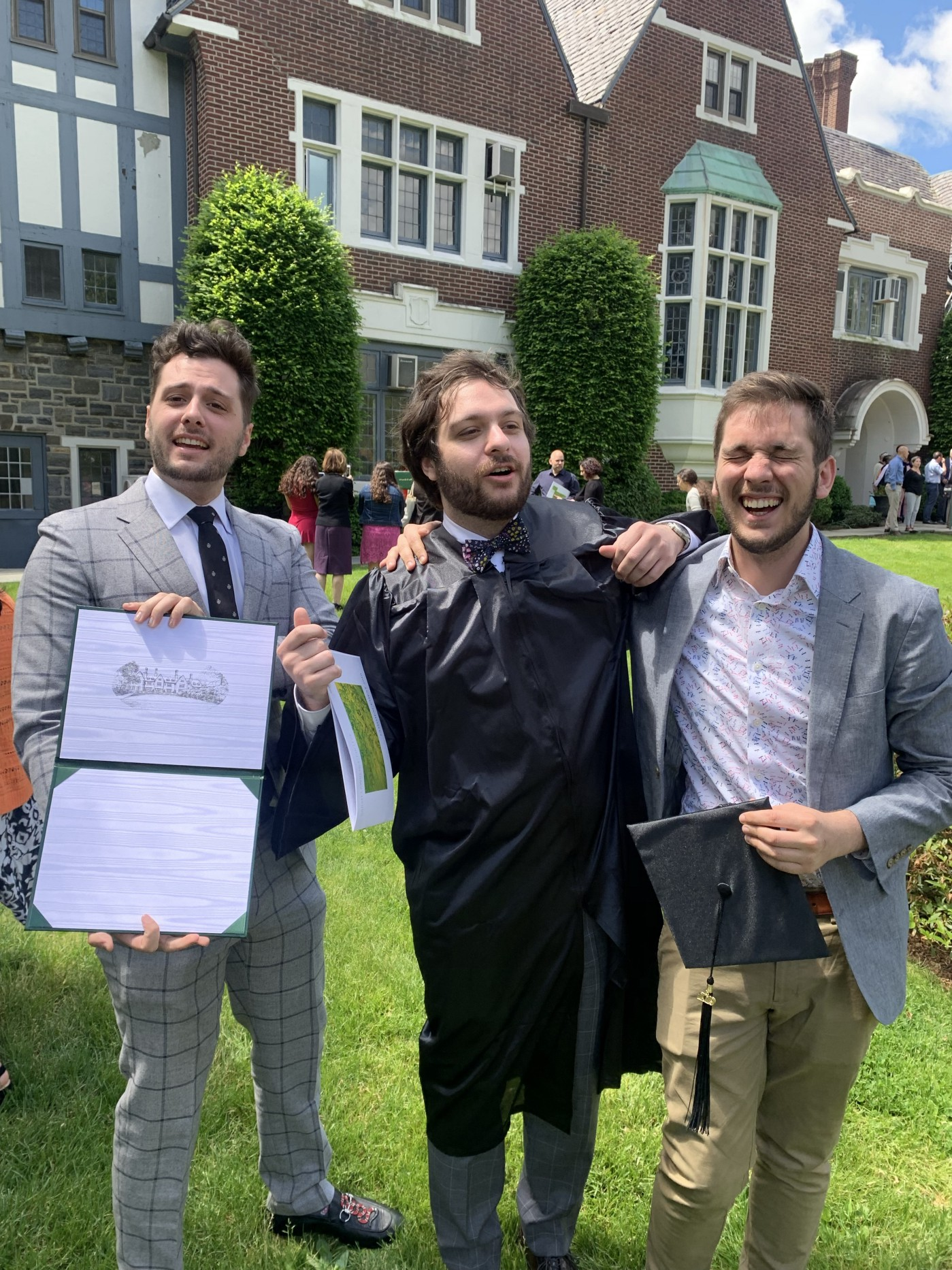 A picture of me wearing a suit, next to my two brothers at my middle brother's college graduation.