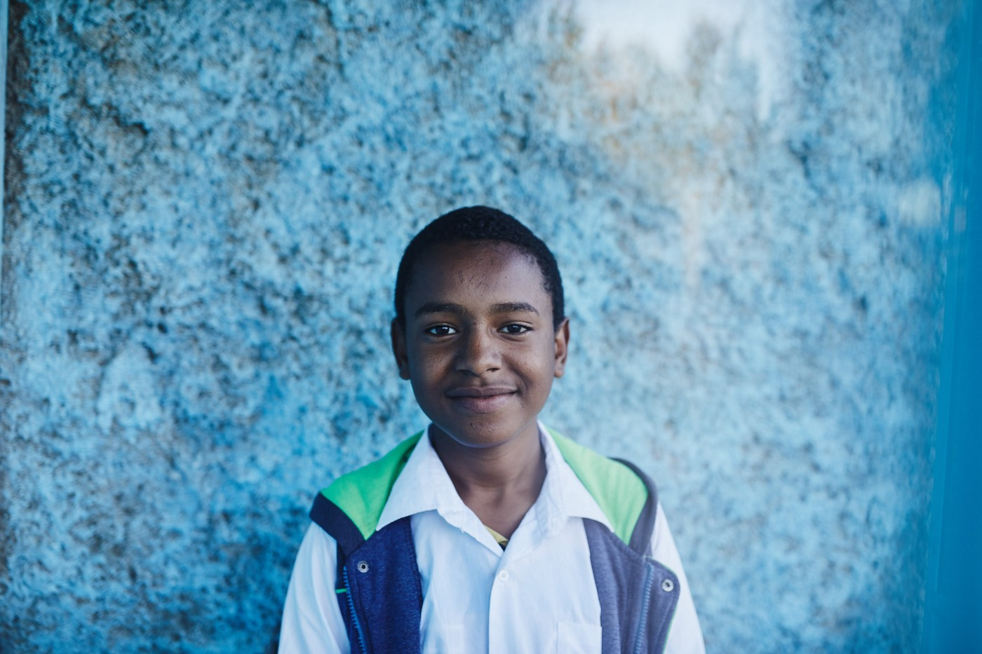 A Ethiopian boy stands in front of a blue wall, in a white button-up shirt and a blue vest.
