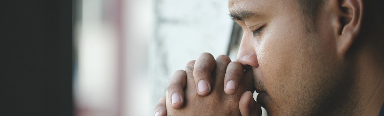 Depressed man sitting in room praying, thoughtful, mindful, unease, worry.