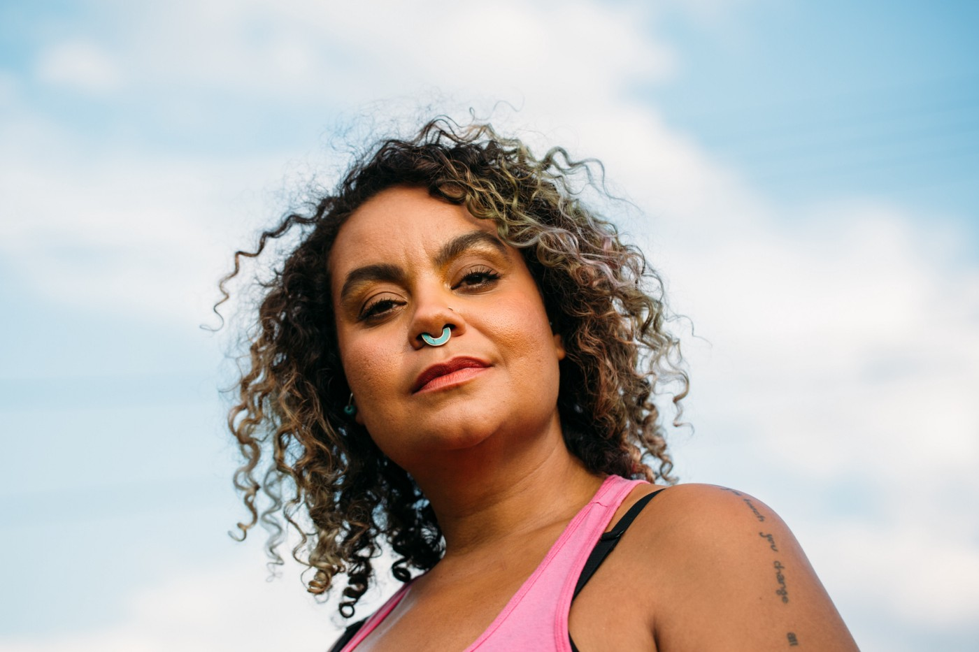 A closeup photo of Adrienne Maree Brown against the sky.