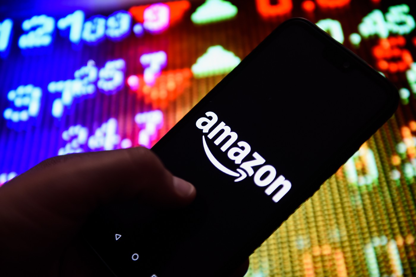 Photo illustration of the Amazon logo displayed on a smart phone against a colorful stock ticker backdrop.