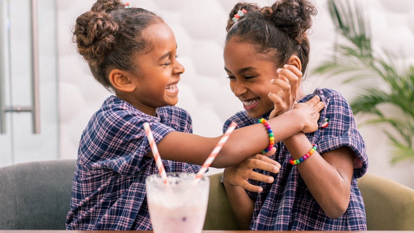 Photo of twin young girls laughing and sharing a milkshake