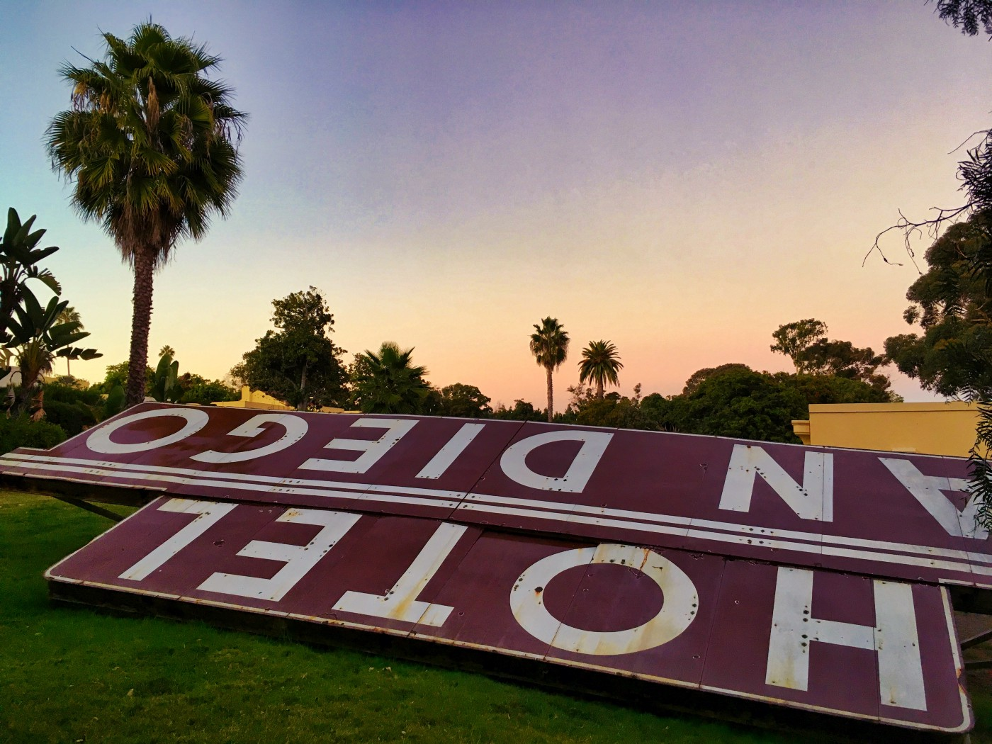 A vintage Hotel San Diego sign lays on the ground with a sunset and palm trees in the background