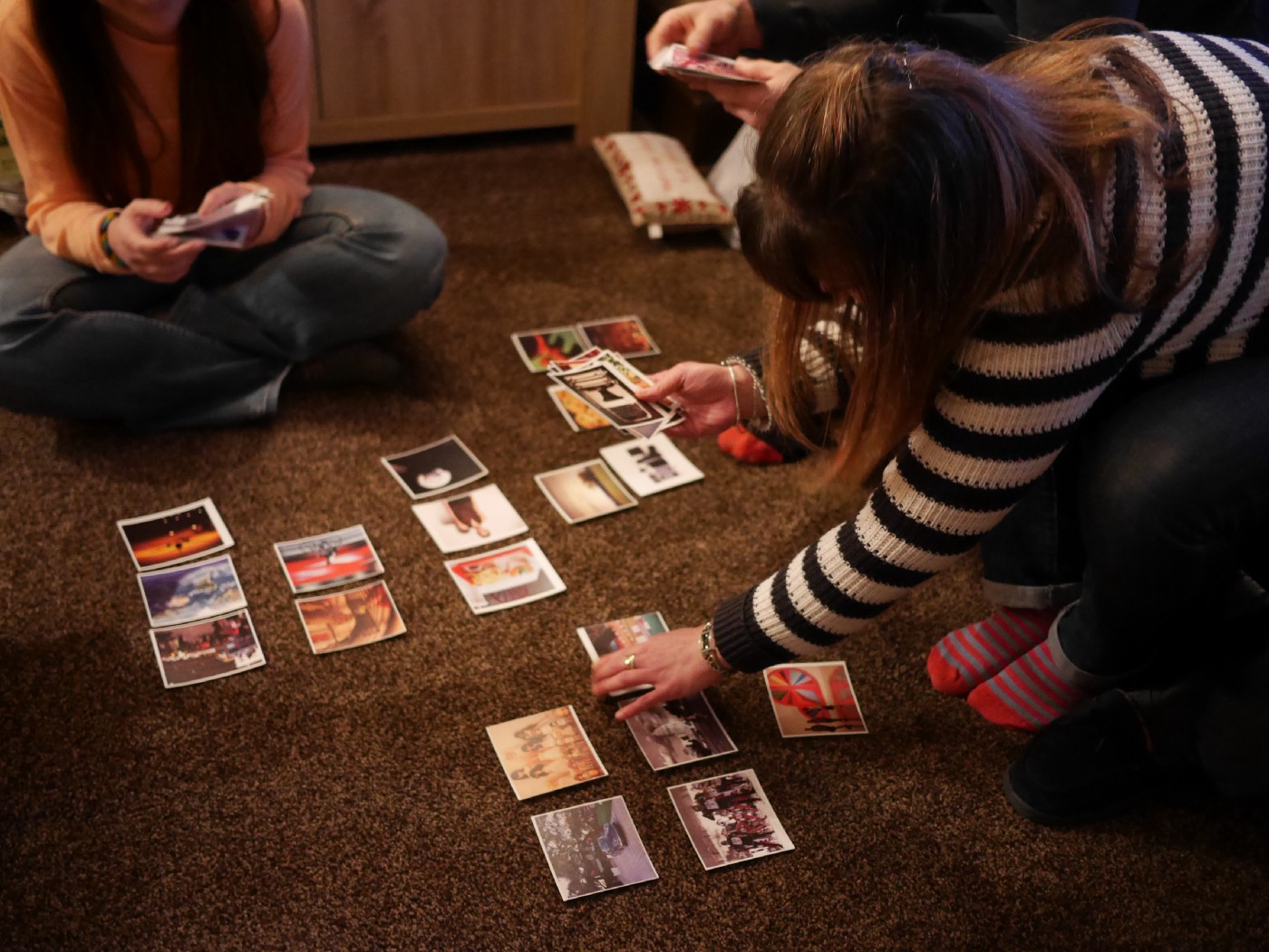 Two people sort photograph cards into groups for a research exercise
