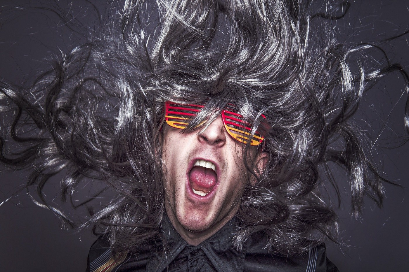 Musician with long, gray, wild hair and red and yellow slatted glasses. He is singing.