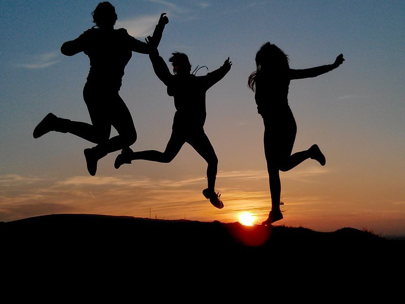 Three people jumping for joy sillhoueted against a setting sun over a mountain.