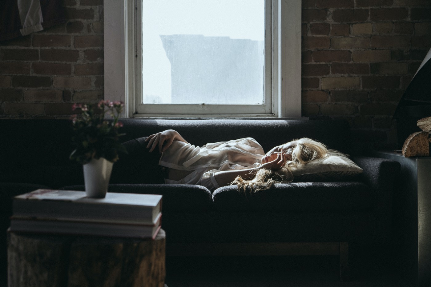 Woman dejectedly lying on a couch with a window behind her.