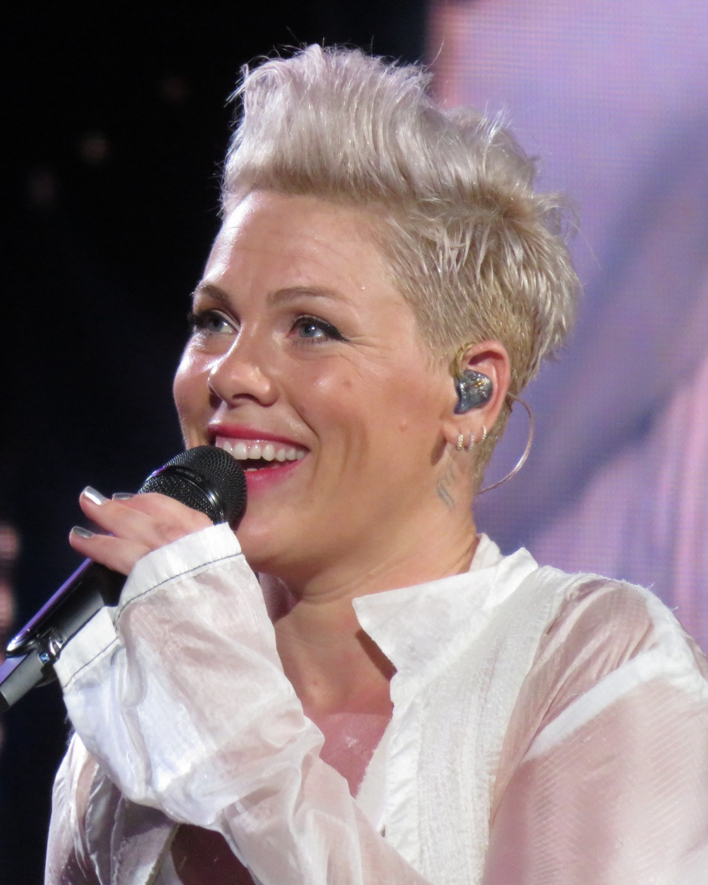 Close up shot of the musician Pink, performing with a microphone and short, blonde hair.