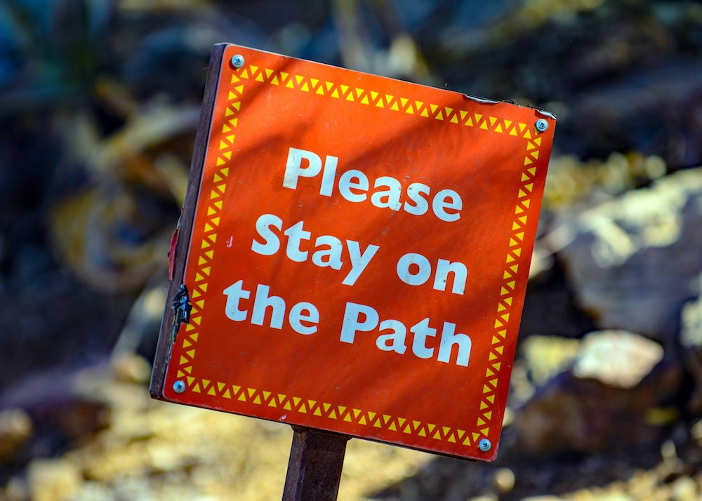 Sign saying to 'Please stay on the path'