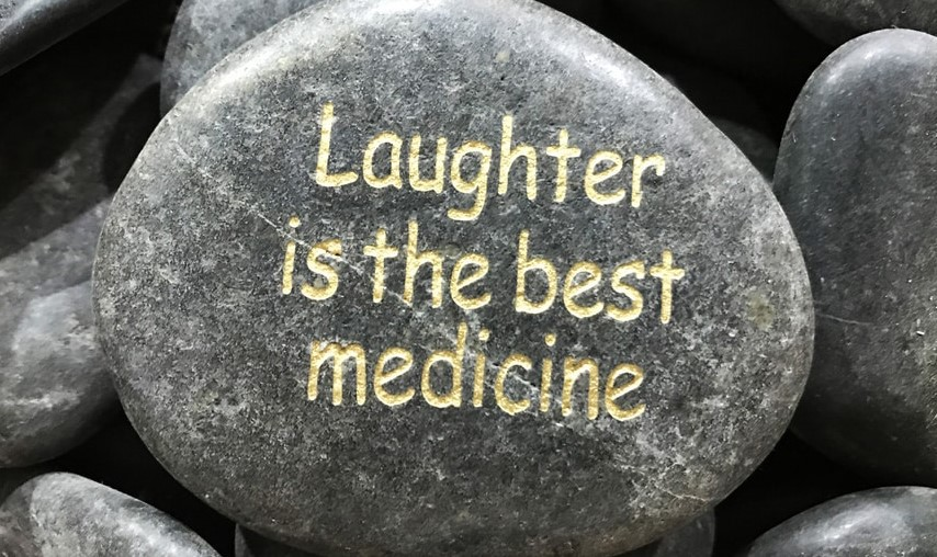 "Gray stone inscribed with the words ""Laughter is the best medicine."""