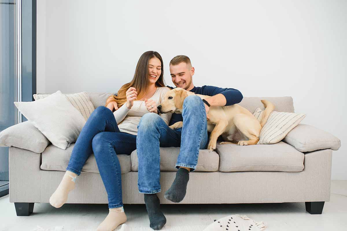 couple on couch with their dog