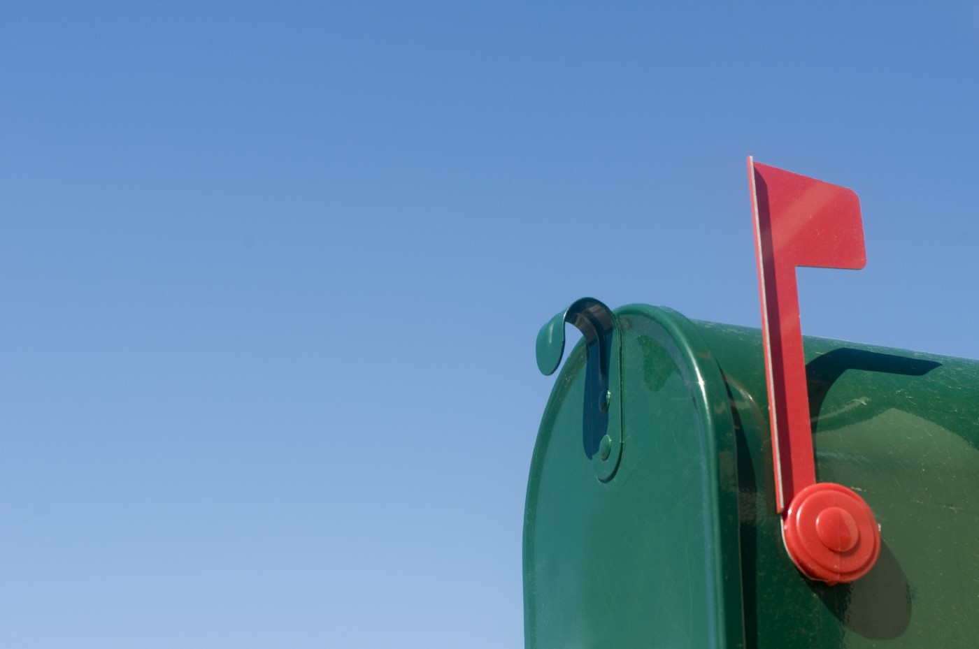 Outgoing mail in green mailbox with a red flag in upright position.