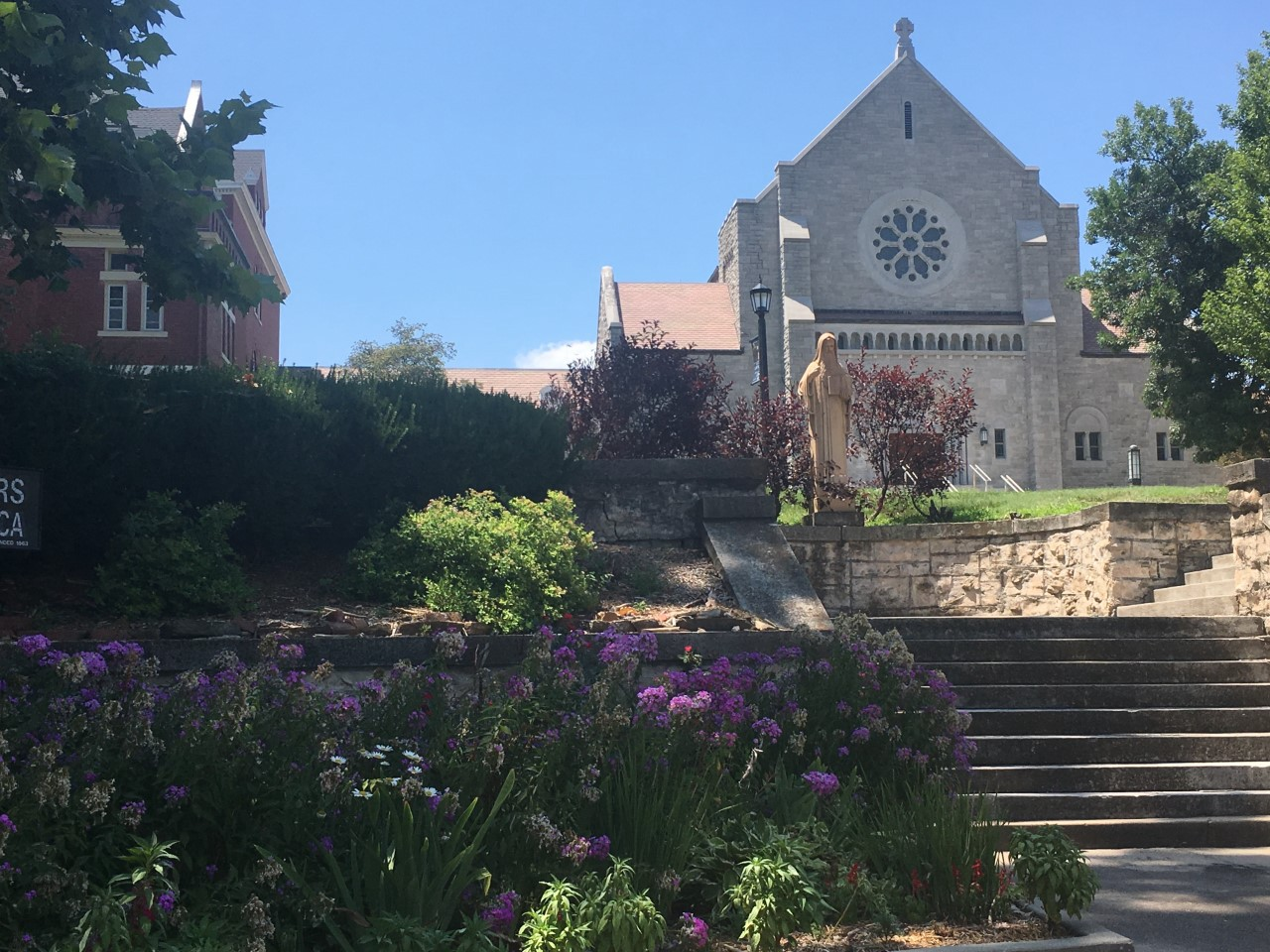 A garden with violet prairie flowers frames the granite facade of St. Scholastica Chapel in Atchison, KS.