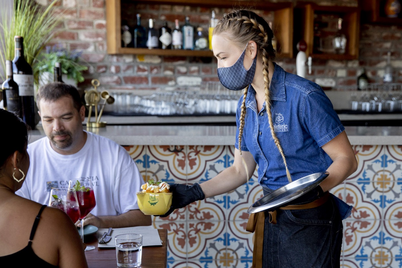 A man and a woman are served at a restaurant. The waitress is wearing a mask, they are not.